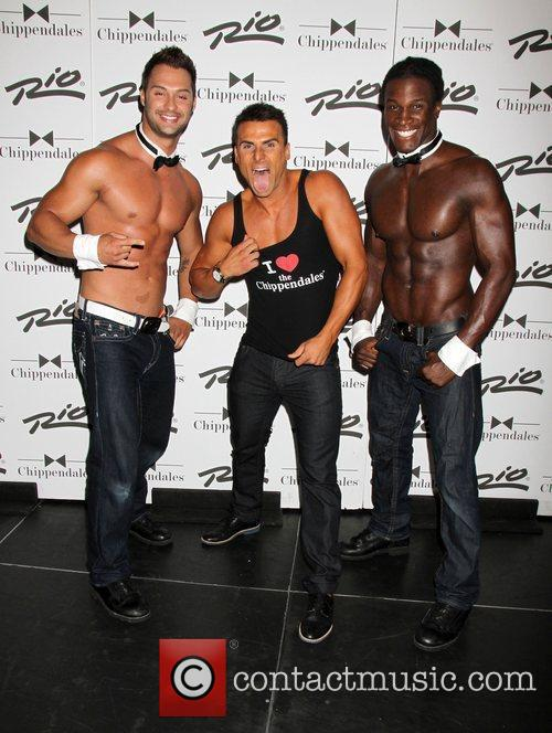 Poses with the Chippendales at the Chippendales Theater...