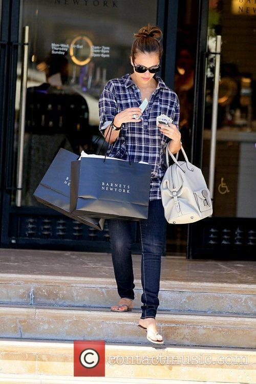 Shows off her baby bump while exiting Barney's...