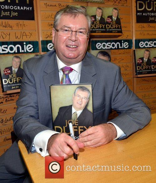 Signs copies of his autobiography 'Just Joe' at...
