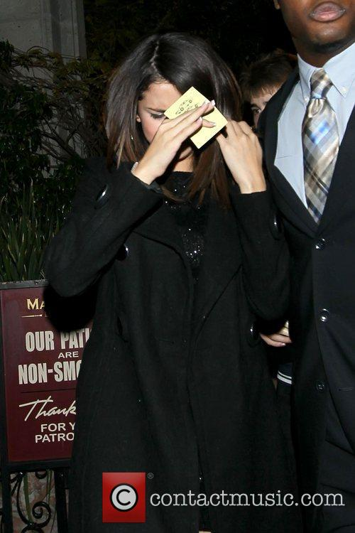 Keeps her face covered as she arrives at...