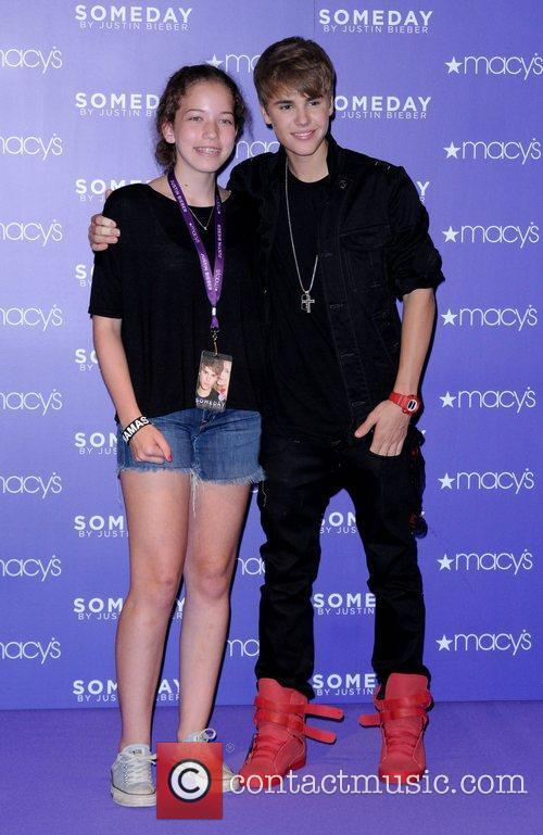 Justin Bieber poses with a fan Justin Bieber...