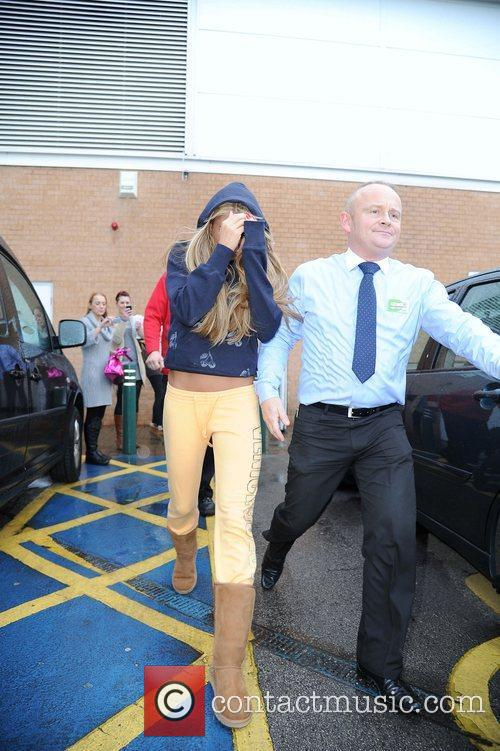 Katie Price hides her face as she leaves...