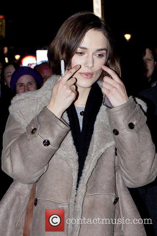 Keira Knightley wipes her hair out of her...