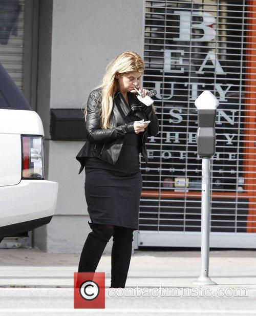 Kirstie Alley  smoking a cigarette while out...
