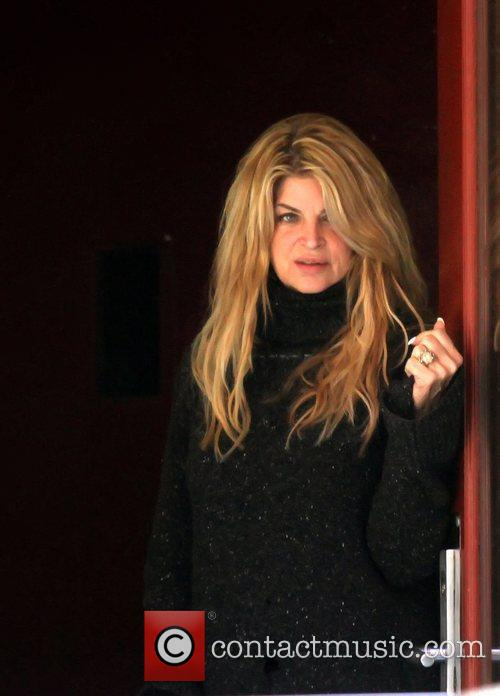 Kirstie Alley looking out of a door at...