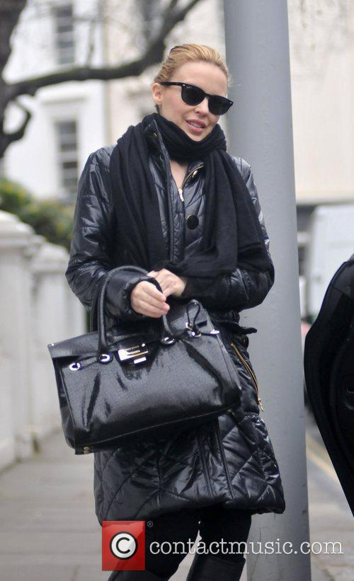 Kylie Minogue leaving her home wearing sunglasses and...