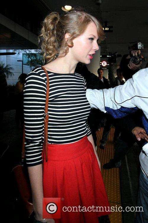 Taylor Swift wearing a striped shirt as she...
