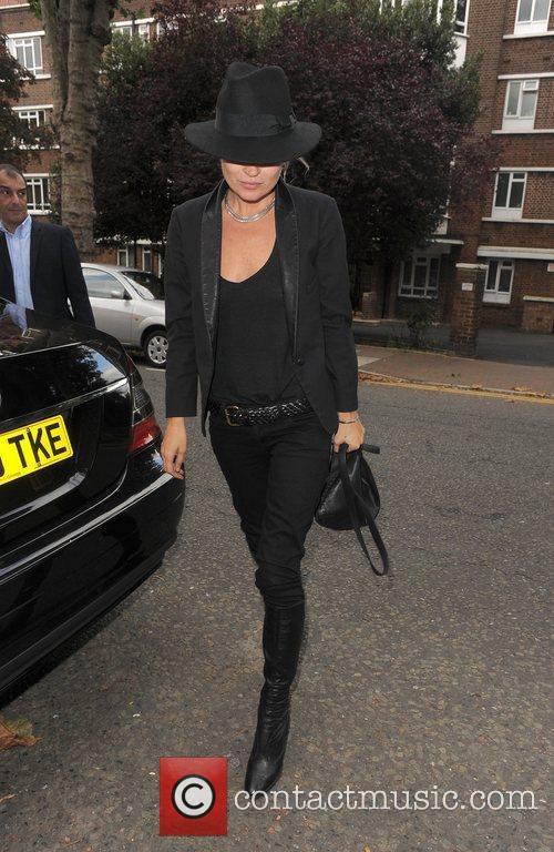 Kate Moss hides her face under a black...