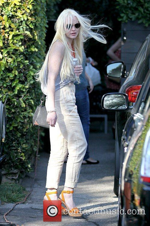Lindsay Lohan showing off her styled hair as...