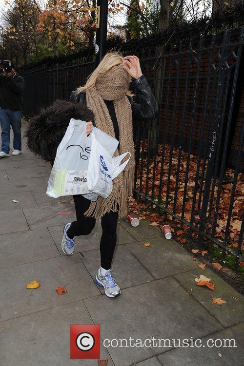 Michelle Collins hides her face with a scarf...