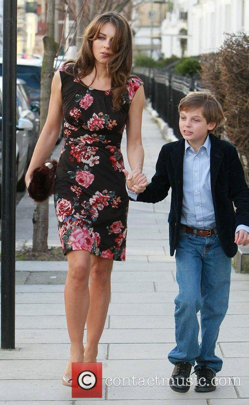 Leaving her home with her son Damian Hurley...
