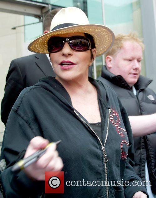 Liza Minnelli wearing a hat and sunglasses as...