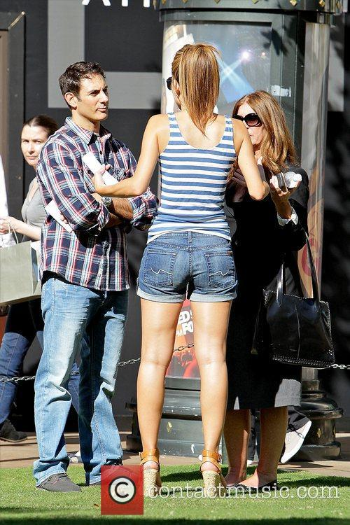 Wearing denim shorts and wedge sandals as she...