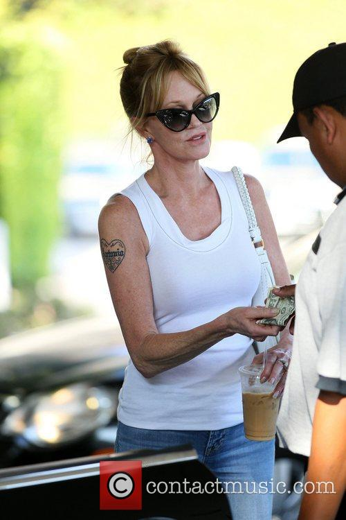Melanie Griffith holding cash to pay the valet...