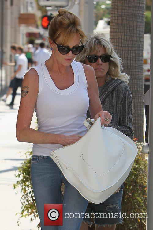 Melanie Griffith returns to her car to feed...