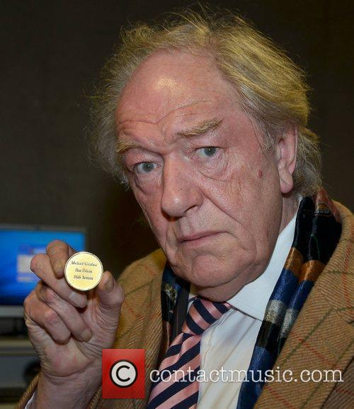 Is presented with the Gold Medal for Honorary...