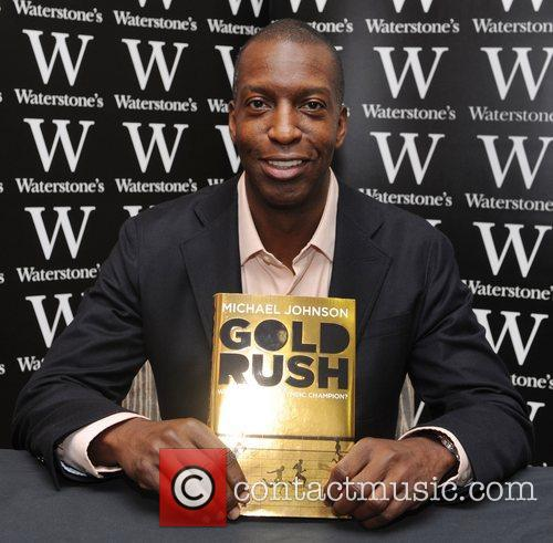 Michael Johnson  signs copies of his book...