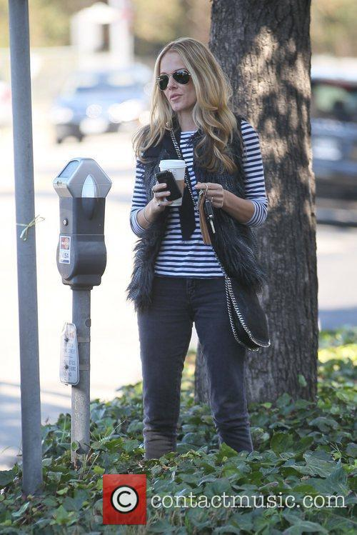 Monet Mazur paying a parking meter while on...