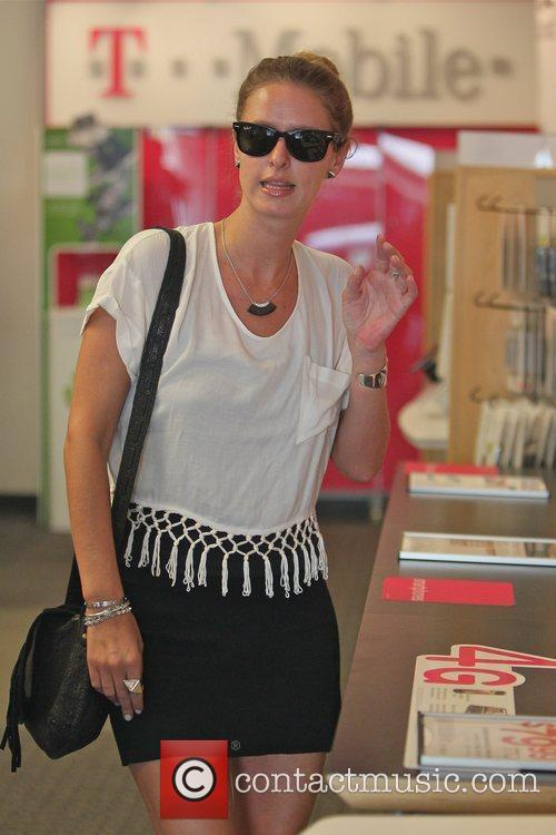 Nicky Hilton looking at mobile phones at a...