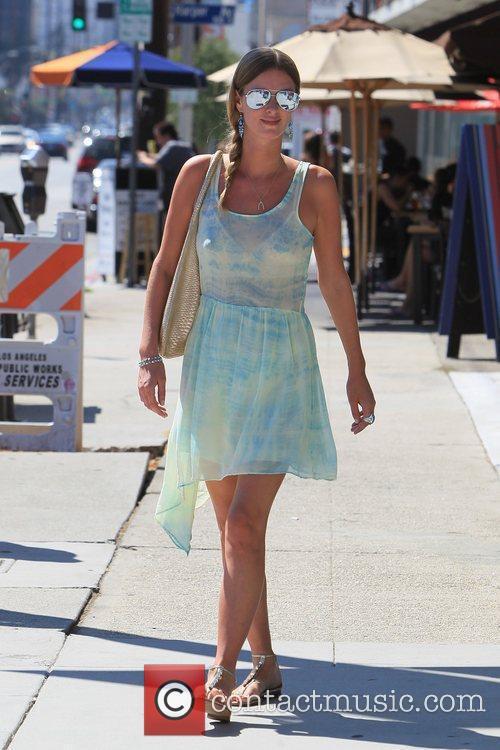 Wearing a teal tie dye dress as she...