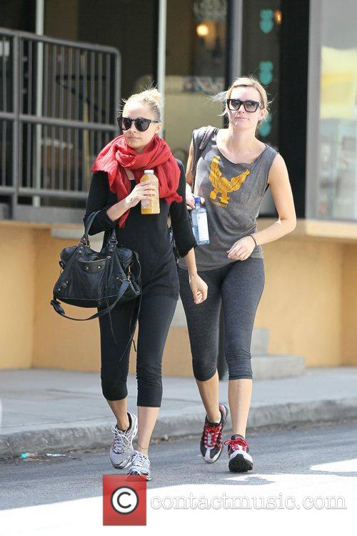Nicole Richie, wearing a chunky red scarf and...