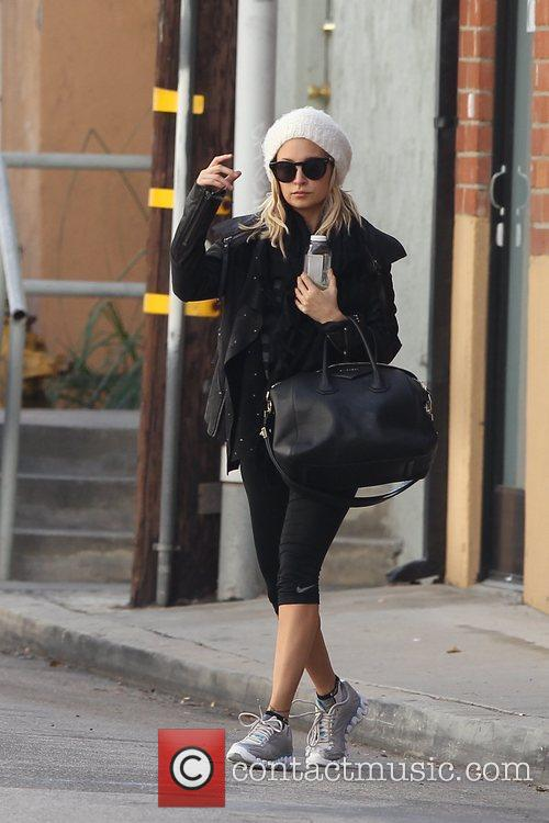 Nicole Richie wearing a white winter hat as...