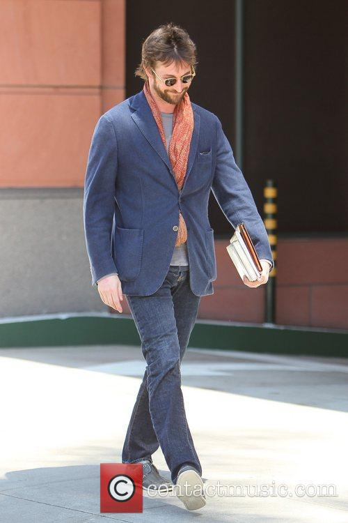 Noah Wyle carrying books and his iPad as...