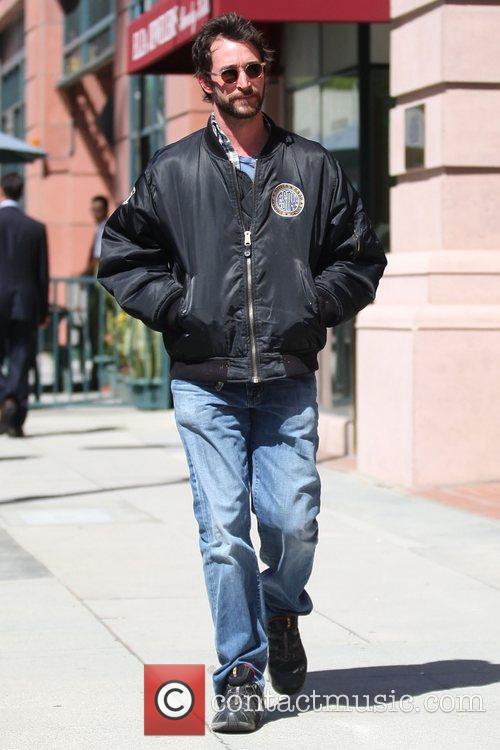 Noah Wyle wearing a bomber jacket as he...