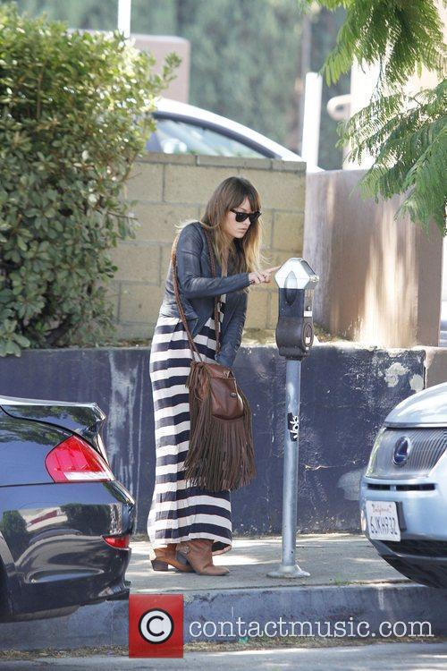 Olivia Wilde pays money into a parking meter...