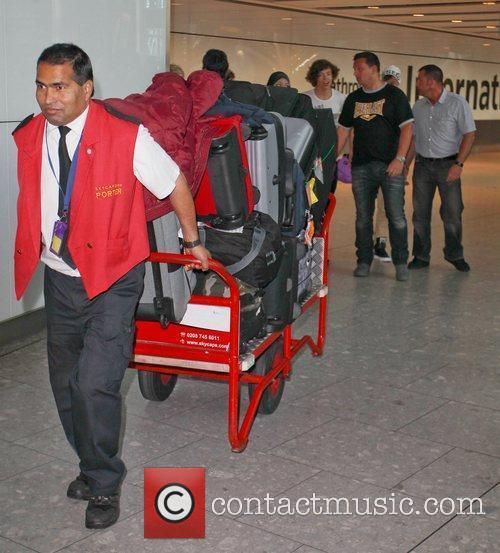 An airport security man pulls One Direction's suitcases...