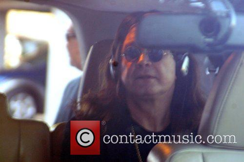 Ozzy Osbourne listens with his headphones as he...