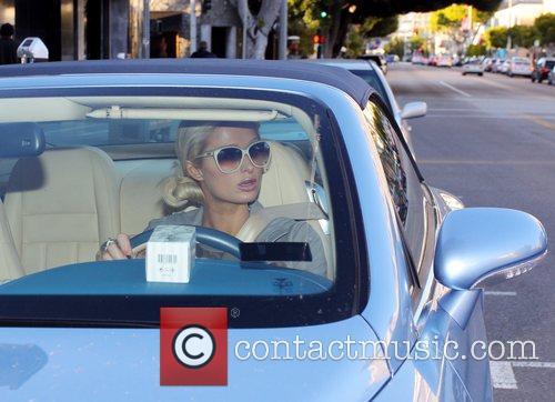 Paris Hilton drivers away in her blue Bentley...