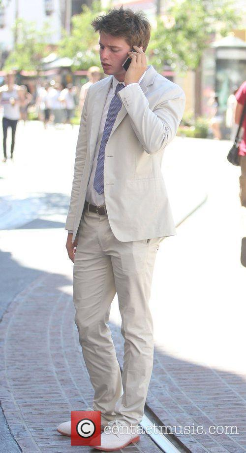 Patrick Schwarzenegger wearing a white suit and shoes...