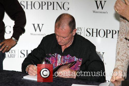 Signs copies of his book 'Glorious: My World,...