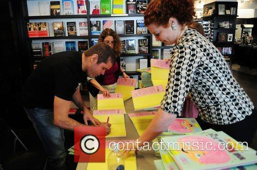 Signs copies of his book 'The Boy With...