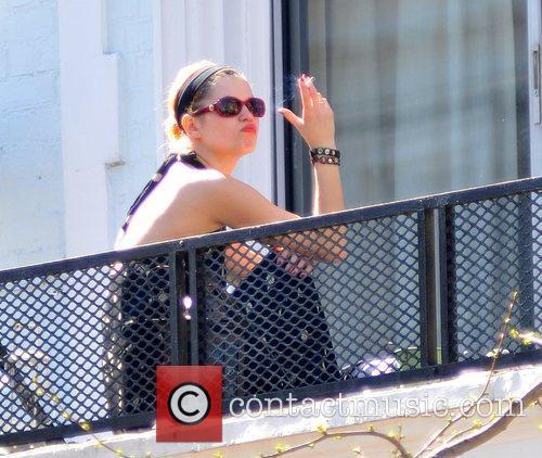 Pixie Geldof smokes a cigarette on a balcony...