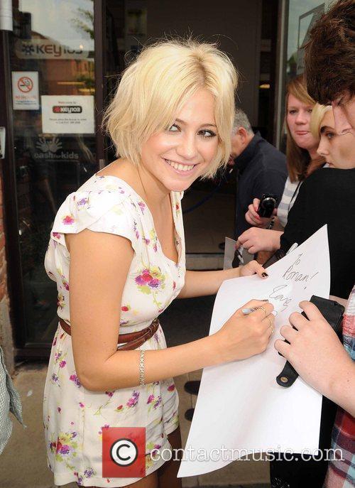 Pixie Lott signs an autograph for a fan...