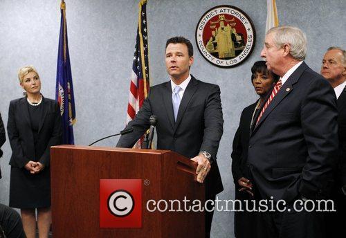 Deputy District Attorney David Walgren, center, makes a...
