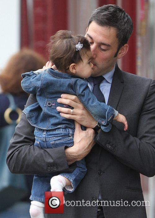 Alex Bourne  carries his daughter Amelie in...