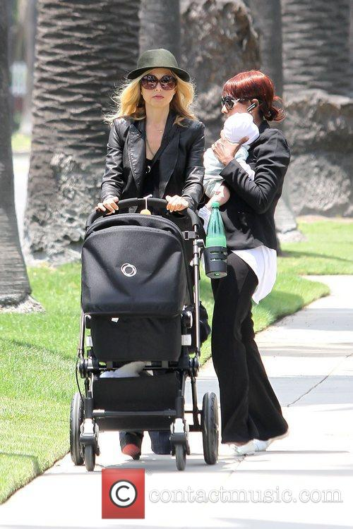 Pushing a stroller as she walks with her...