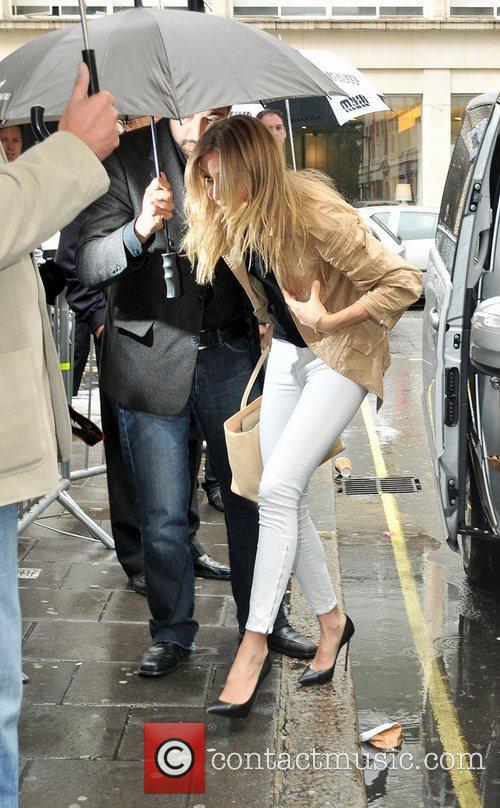 Cameron Diaz is protected by an umbrella from...
