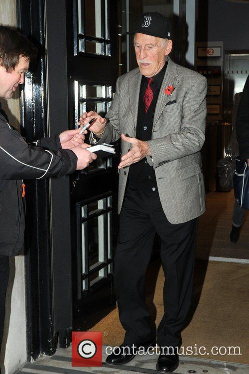 Bruce Forsyth signs an autograph for a fan...