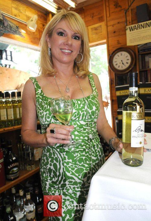 Ramona Singer signs bottles of her signature wine...
