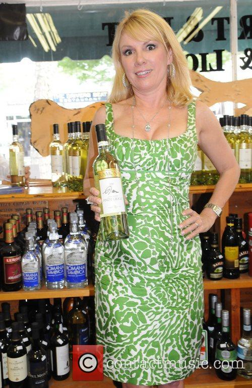 Signs bottles of her signature wine Pinot Grigio...
