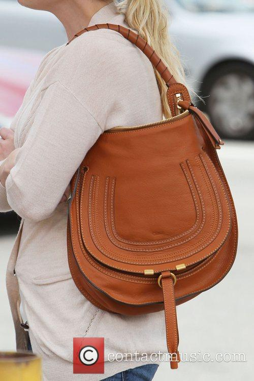 Reese Witherspoon carries a tan coloured designer bag...