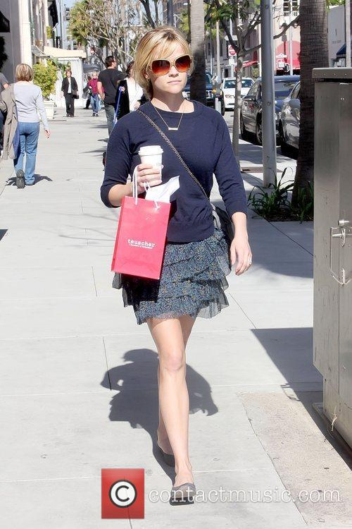 Carrying a to-go coffee as she shops in...