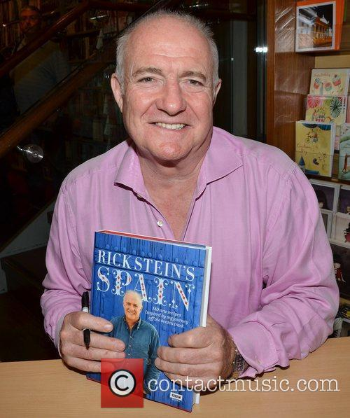 Signs copies of his book 'Rick Stein's Spain'...