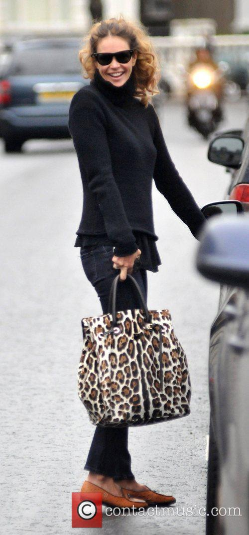 Elle Macpherson returns to her car after taking...