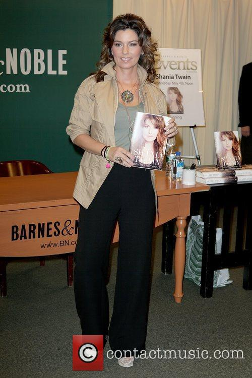 Signs her new book 'From This Moment On'...