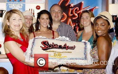 Cast members celebrate the 100th performance of the...